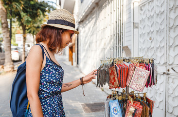 Positive young brunette girl choosing a fabric purse at outdoor turkish market
