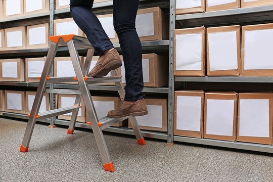 Woman climbing up ladder in archive