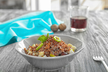 Plate with quinoa salad on wooden table