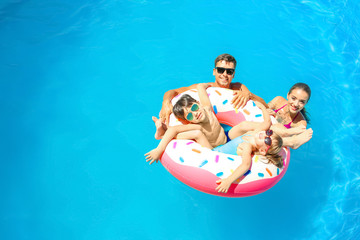 Happy family with inflatable donut in swimming pool
