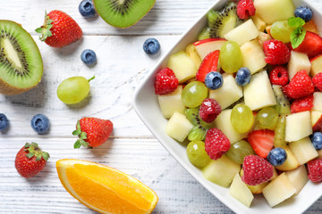 Bowl with yummy fruit salad on wooden table