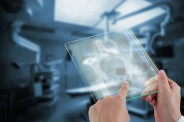 Composite image of hands of female doctor using digital tablet