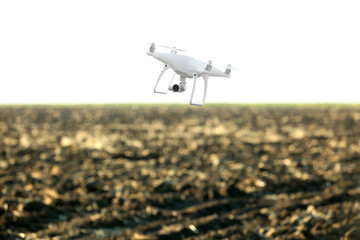 Modern quadcopter flying over field