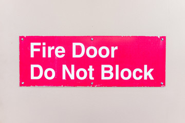 Closeup of red sign with fire door do not block words warning