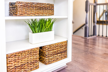 Closeup of white, modern, minimalist shelves in kitchen or living room with woven baskets and green plants pots, containers