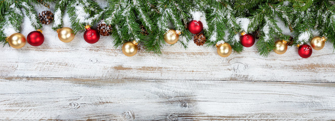 Christmas branches with golden and red ornaments with snow on rustic white wooden background