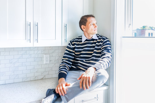 Young man sitting on modern new kitchen countertop by window looking outside thinking