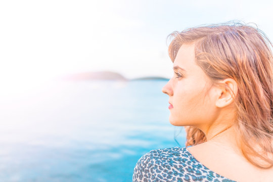 Profile portrait of young happy smiling woman sitting on edge of dock in Bar Harbor, Maine looking to side during sunset with golden sunlight and tan skin
