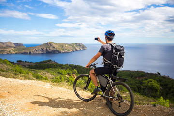 a young guy on a mountain bike trails in Spain and takes a photo on a white phone in the background of the Mediterranean sea of the rocky coast of the Costa Brava.