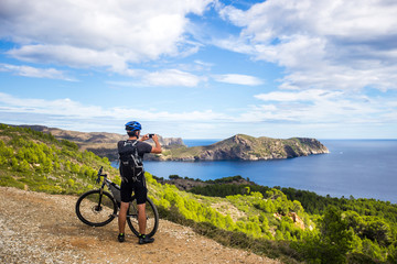 a young guy on a mountain bike trails in Spain and takes a photo on a white phone in the background of the Mediterranean sea of the rocky coast of the Costa Brava. k.