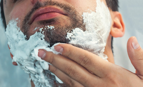 A young man is shaving in the morning, smiling. On the face there is a lot of foam for shaving. Toning