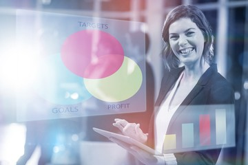 Composite image of business woman working on digital tablet
