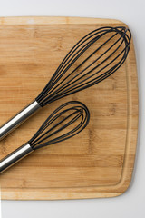 Two Whisks Angled on a Wooden Cutting Board