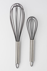 Two Whisks on White Background Top View