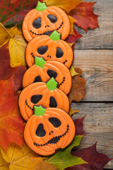 Homemade gingerbread cookies in the shape of pumpkins for Halloween. Autumn maple leaves on old wooden background. Top view