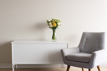 Grey retro armchair next to white sideboard with glass vase of cream and yellow flowers against neutral wall backgroundp
