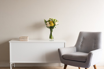 Grey retro armchair next to white sideboard with rattan box and glass vase of cream and yellow flowers against neutral wall background