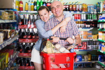 Smiling family couple with shopping basket