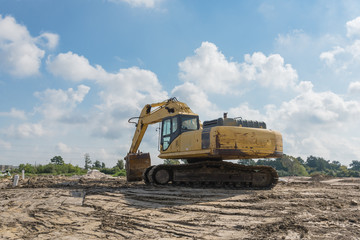 Excavator with digger standing for earthmoving works at construction site with storm cloud blue sky in Houston, Texas, USA. Framework for the concrete foundation of new building. Machinery background