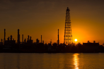 Silhouette oil refinery and petrochemical plant at sunrise time beside Chao Phaya river, Thailand. Light reflection on the smooth water.