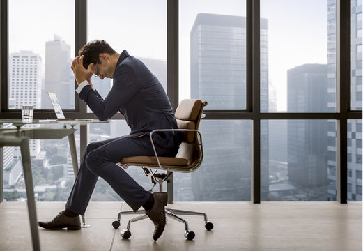 Stressed young businessman overworking