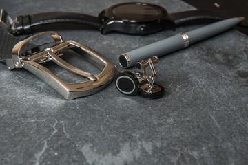 Elegant men`s business accessories. Black watches, belt, pen, cufflinks on luxury stone table..