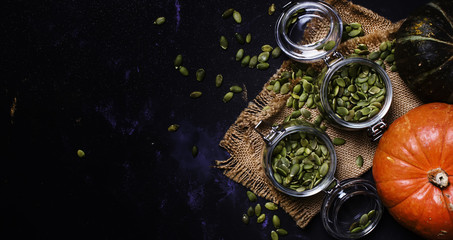 Raw pumpkin seeds in glass jar, black background, top view