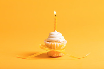 Cupcake with candle celebration theme on a yellow background