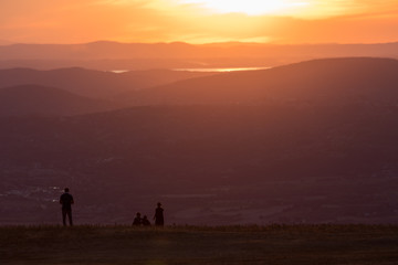 A family on a mountain peak looking over a valley at sunset