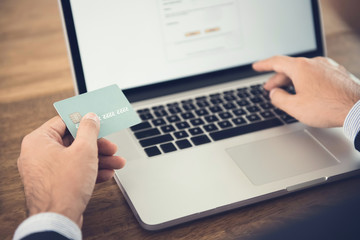 Businessman using laptop computer shopping online and paying with credit card