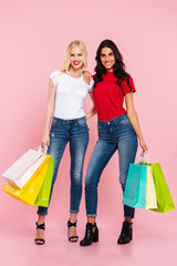 Full length image of two smiling women hugging with packages