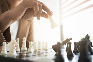 business executive playing chess on board in office, strategy and competition concept