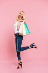Vertical side view of happy blonde woman posing with packages