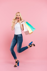 Full length image of shocked blonde woman moving with packages