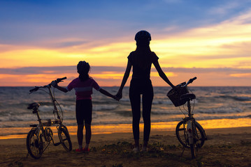 Silhouettes of biker family on the beach at beautiful sunset.