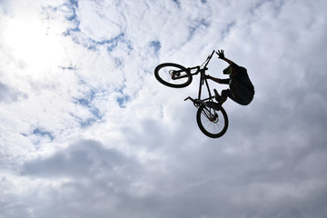 Silhouette of a young man freestyle stunt cyclist flying in the sky