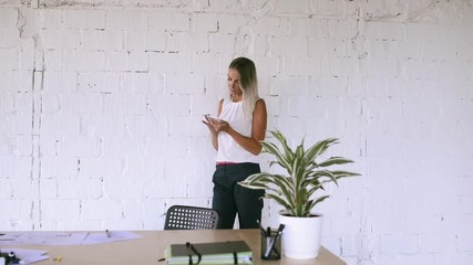 Wall Mural - Businesswoman in her office with a smartphone.