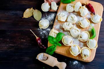 Fototapeta Raw dumplings with meat with flour on dark background