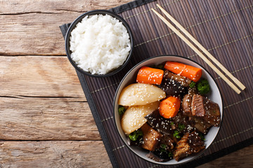 Korean stewed beef short ribs with vegetables and rice garnish close-up. Horizontal top view
