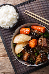 Galbi jjim Korean Braised Beef Short Ribs with rice close-up. vertical top view