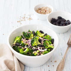 Broccoli with raisins, red onions and seeds in a white bowl on a blue wooden background,  selective focus. Healthy raw diet salad