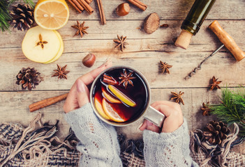 A cup of mulled wine in his hands. Selective focus.