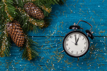 Photo of Christmas branches of fir, cones and clocks, snow