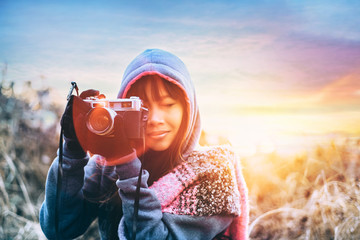 Young female photographer in cold weather wearing sweater and colorful scarf during afternoon sunset outside