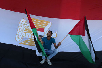 A man holds Palestinian flags as an Egyptian flag is seen in the background during celebrations after Hamas said it reached a deal with Palestinian rival Fatah, in the central Gaza Strip