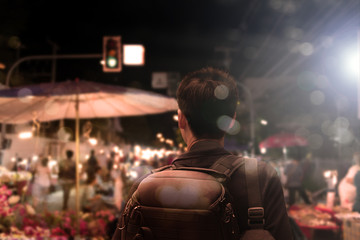 Male tourist sightseeing flea market,traveling concept.Street photographer wandering on famous night walking street in chiengmai city, northern Thailand.