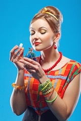Young woman in colorful old-fashion clothes in pin up style holding an opened bottle of perfume and smelling it