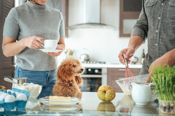 Couple with dog is making breakfast . Couple on the kitchen cooking together.