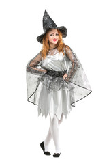 halloween, mystic, holidays concept. isoalted red haired charming witch wearing pointy hat, silver dress with light shawl decorated with shining web and black shoes on white background