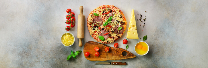 Girl hands making, decopating, preparing pizza with basil leaves on grey light background. Top view, copy space. Banner